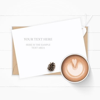 Flat lay top view elegant white composition paper kraft envelope pine cone and coffee on wooden background.