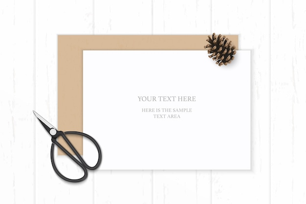 Flat lay top view elegant white composition paper kraft envelope pine cone and vintage metal scissors on wooden background.