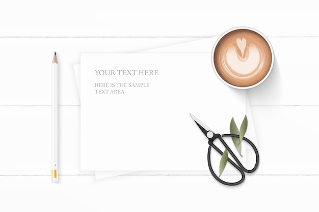 Flat lay top view elegant white composition paper nature leaf coffee pencil and vintage metal scissors on wooden background.