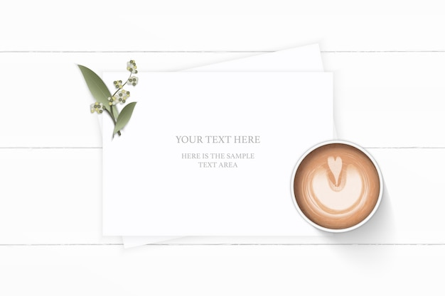 Flat lay top view elegant white composition paper plant leaf flower and coffee on wooden background.
