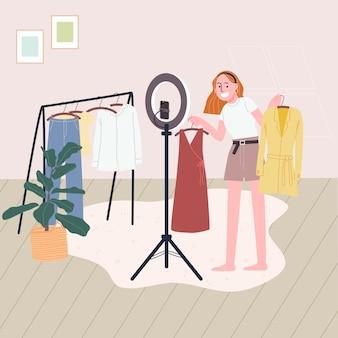 집에서 라이브 비디오를 방송하는 동안 온라인으로 옷을 판매하는 만화 여자 캐릭터의 플랫 스타일 일러스트. 전자 상거래, 온라인 판매, 라이브 스트리밍의 개념.