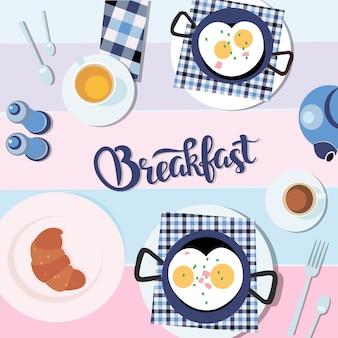スクランブルエッグ、紅茶健康食品flatlayのカップとクロワッサン。