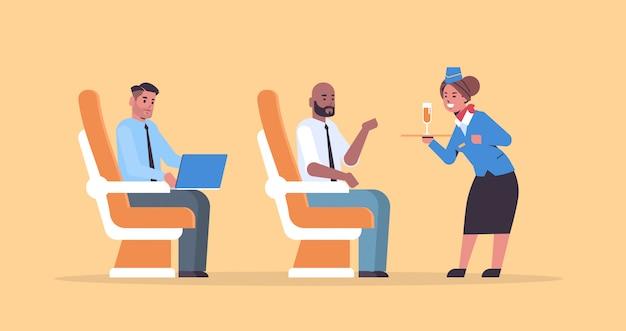 シャンパングラスのプロフェッショナルサービス旅行の概念と制服保持トレイで飛行機のボードの乗客スチュワーデスにアルコール飲料を提供する客室乗務員