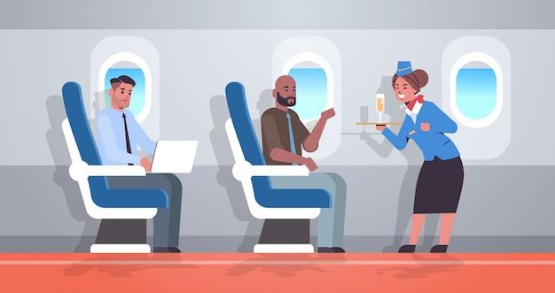 乗務員に乗ってスチュワーデスの乗客にアルコール飲料を提供するシャンパングラスの均一な保持トレイでスチュワーデスプロフェッショナルサービス旅行コンセプト飛行機ボードインテリア全長水平