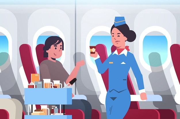 Flight attendant serving drinks to passenger stewardess in uniform pushing trolley cart professional service travel concept modern airplane board interior portrait horizontal flat