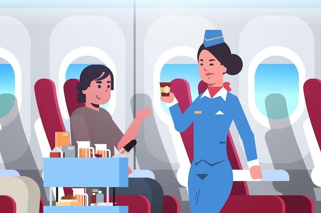 Flight attendant serving drinks to passenger stewardess in uniform pushing trolley cart professional service travel concept modern airplane board interior portrait