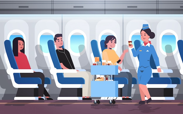 Flight attendant serving drinks to passengers stewardess in uniform pushing trolley cart professional service travel concept modern airplane board interior full length horizontal flat