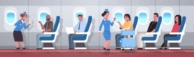 Flight attendants serving mix race passengers stewardesses in uniform offering drinks professional service travel concept modern airplane board interior full length horizontal flat