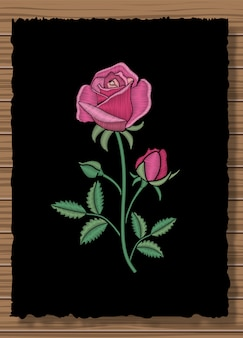 Floral stitched ornament with stitch rose. embroidery flower on a dark flap cloth and wooden texture background.