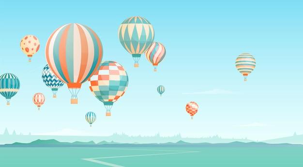 空のイラストで飛んでいる熱気球。地平線の風景に浮かぶ航空機。