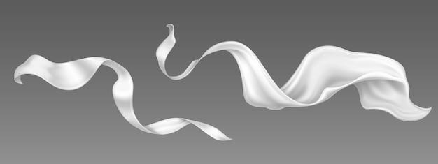 フライングホワイトのシルクリボンとサテン生地。風が吹く中で渦巻くベルベットの服、スカーフまたはケープの現実的なセット。豪華な白い織物のカーテン、灰色の背景に分離された流れるティッシュ