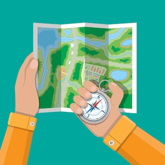 Folded paper city map and compass in hands