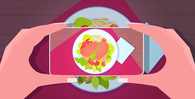 블로그 소셜 미디어 블로그 개념 가로 신선한 준비 접시의 사진을 복용 스마트 폰을 사용하는 음식 블로거