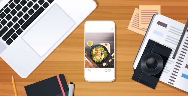 Food blogger workplace laptop keyboard digital camera and smartphone displaying salad on screen blogging concept desktop top angle view horizontal  illustration