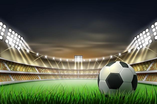 スポットライトに照らされたリアルな緑の芝生でボールとサッカーサッカースタジアムの背景