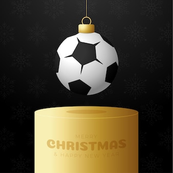 축구 스포츠 크리스마스 값싼 물건 받침대입니다. 메리 크리스마스 스포츠 인사말 카드입니다. 실 축구, 축구공을 검정색 배경의 황금 연단에 크리스마스 공으로 매달아 보세요. 스포츠 벡터 일러스트 레이 션.