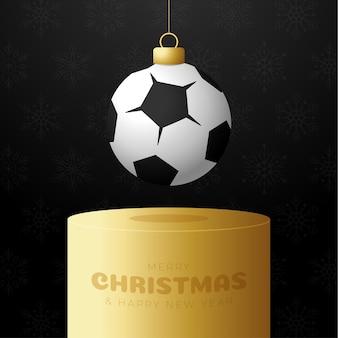 Football sport christmas bauble pedestal. merry christmas sport greeting card. hang on a thread soccer, football ball as a xmas ball on golden podium on black background. sport vector illustration.