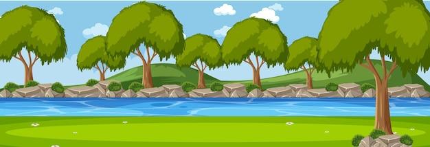 木々がたくさんある昼間の川の水平方向のシーンに沿った森