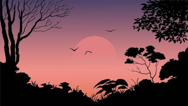 夕日と飛んでいる鳥と森のシルエットの風景