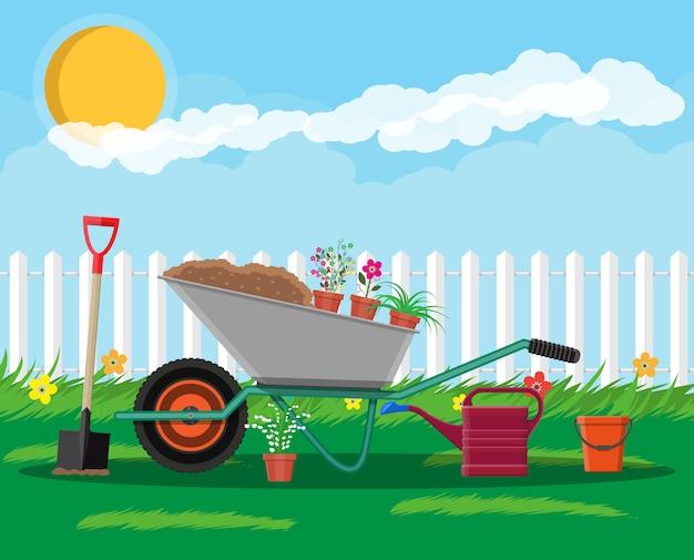 手押し車、花、シャベルのある正式な庭園