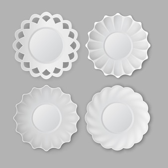 Четыре круглые старинные пустые керамические белые тарелки на сером фоне