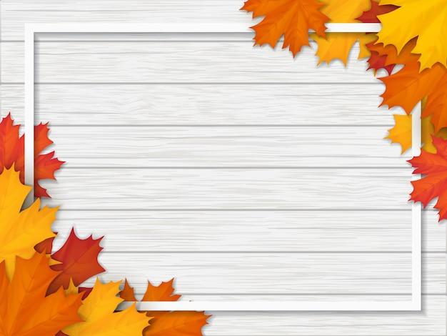 落ちたカエデの葉で飾られたフレーム。木製のヴィンテージテーブルの表面の白い背景に紅葉。