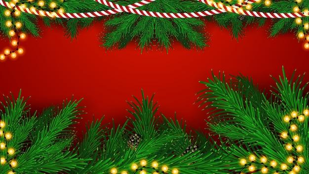 クリスマスツリーの枝と花輪のフレーム