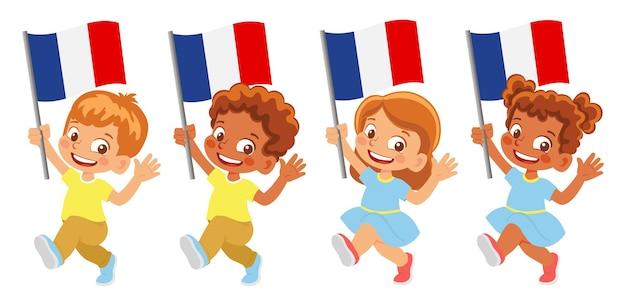 Флаг франции в руке. дети держат флаг. государственный флаг франции
