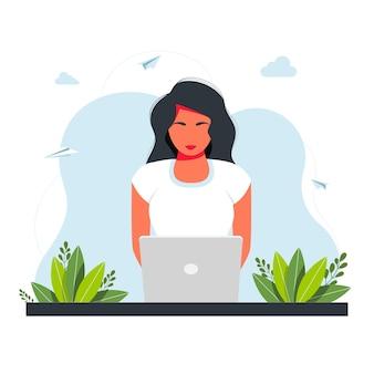 프리랜서, 온라인 공부, 집 개념에서 일합니다. 노트북과 함께 앉아 소녀입니다. 그 소녀는 탁자에 앉아서 배경에 가정용 식물이 있는 노트북에서 일합니다. 프리랜서 개념