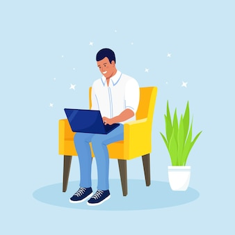 椅子に座ってお金を稼ぐフリーランサー。フリーランスで効果的かつ生産的な仕事。ホームオフィスの職場。彼のラップトップからリモートで作業している人々
