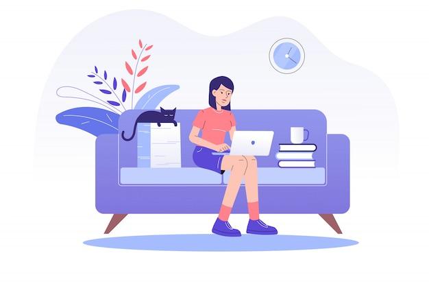 ソファーに座って、自宅のラップトップでオンラインで作業するフリーランサーの女性