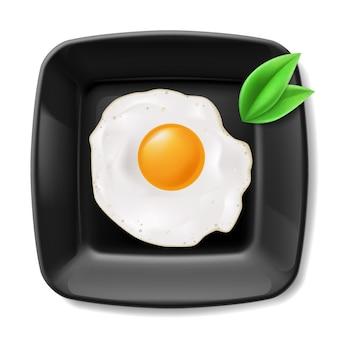 Жареные яйца подают на черной квадратной тарелке. обычный завтрак