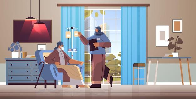 친절한 아랍 간호사 또는 자원 봉사자가 노인 환자 홈 케어 서비스 의료의 드리퍼를 확인합니다.