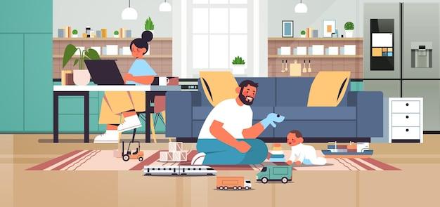 家庭で幼い息子と遊ぶラップトップの父を使用して一緒に時間を過ごすフレンドリーな家族子育ての概念モダンなキッチンインテリア水平全長ベクトル図