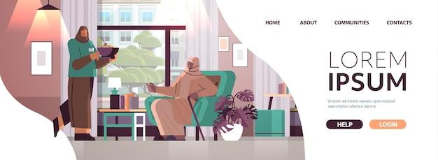 Дружелюбная медсестра или волонтер, приносящий еду арабской пожилой женщине, услуги по уходу на дому, концепция здравоохранения и социальной поддержки, интерьер дома престарелых, горизонтальная полная длина, копия пространства, векторная иллюстрация