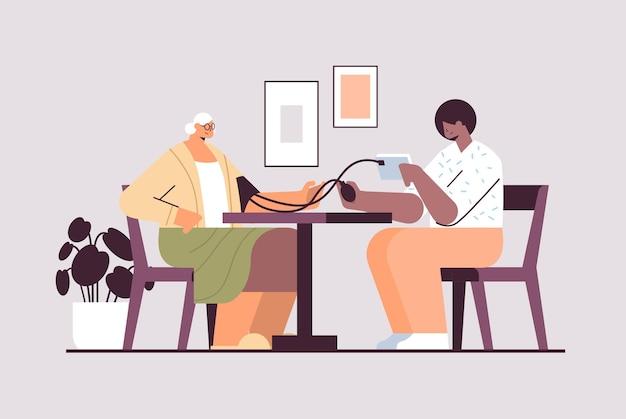 フレンドリーな看護師またはボランティアが高齢の女性に血圧をチェック患者在宅介護サービスヘルスケアおよびソーシャルサポートの概念水平全長