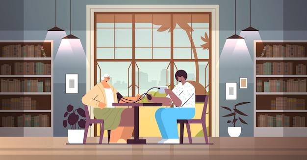 フレンドリーな看護師またはボランティアが高齢の女性に血圧をチェック患者在宅ケアサービスヘルスケアおよびソーシャルサポートの概念ナーシングホームインテリア水平全長