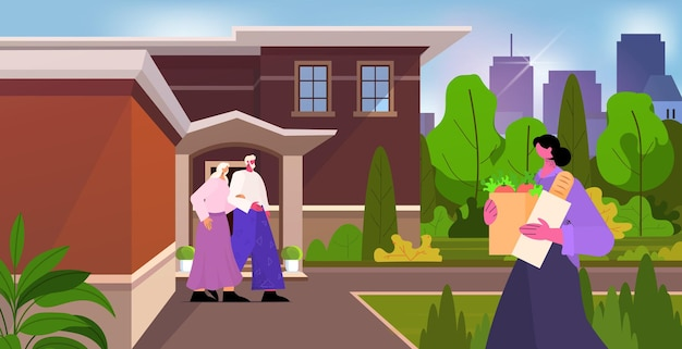 Friendly nurse or volunteer bringing food to senior couple home care services healthcare and social support concept