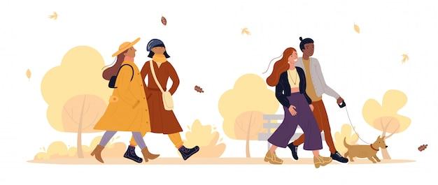 秋の公園で歩いている友人、恋人のカップル