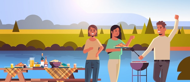 Friends preparing hot dogs on grill man and women having fun picnic barbecue party concept park or river bank landscape background flat portrait horizontal