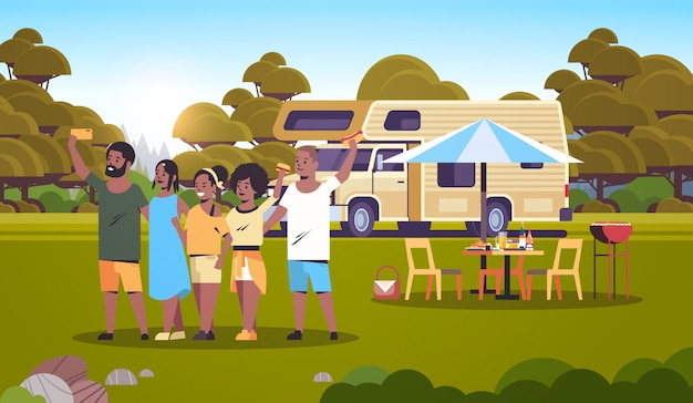Friends taking selfie photo standing at trailer outdoors african american men women group having fun summer picnic barbecue party concept landscape background flat full length horizontal