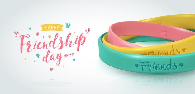 友情日バナー、友好の幸せな休日。親友の黄色、ピンク、ターコイズのゴム製ブレスレット。