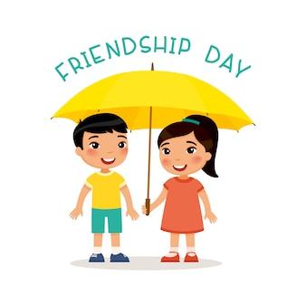 友情の日。かわいい小さなアジアの男の子と女の子は傘のそばに立つ