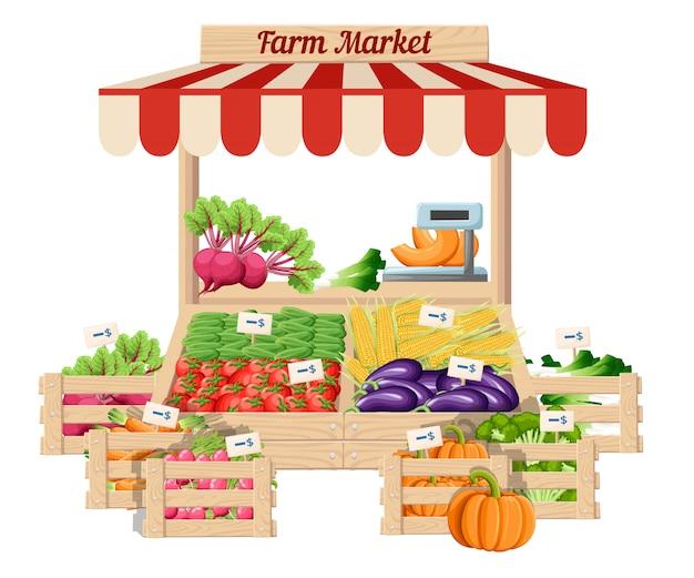 正面の市場の木製スタンドファームフードと野菜の重量と値札の白い背景の上のオープンボックスの野菜