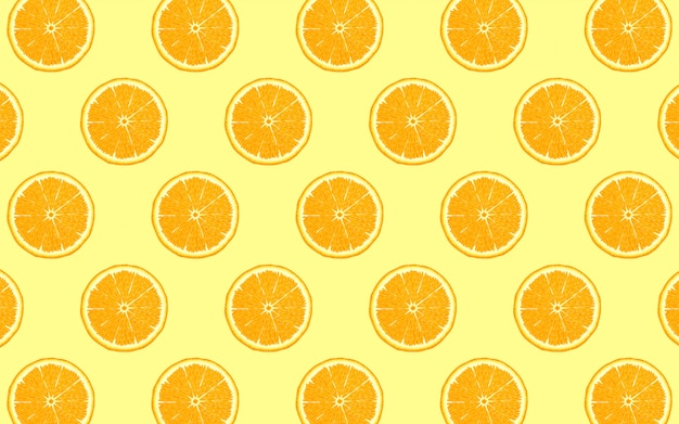 Fruit pattern of fresh orange halves on yellow background. from top view