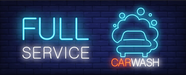 Full service car wash neon sign. vehicle in foam and luminous inscription on brick wall.
