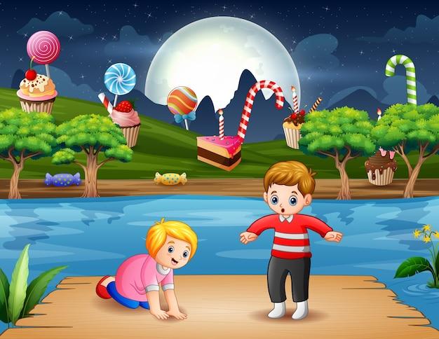 夜の木製の港で面白い子供たち