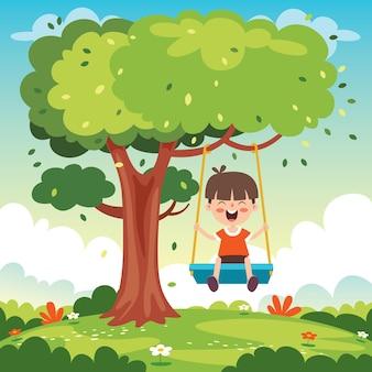 Забавный ребенок играет на качелях
