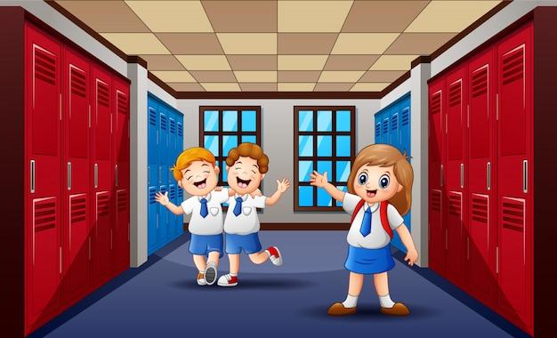 Веселые студенты гуляют и смеются в школьном коридоре