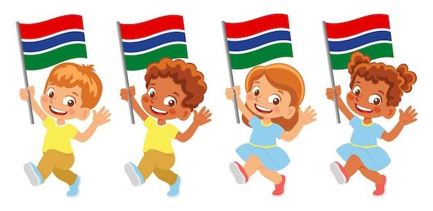 Флаг гамбии в руке. дети держат флаг. государственный флаг гамбии